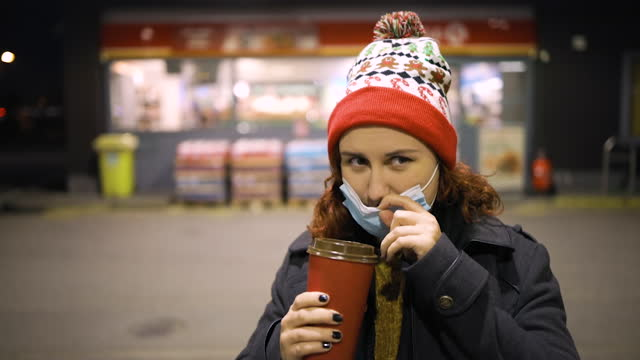 poor woman lowers medical mask to drink coffee wearing xmas hat - coffee drink stock videos & royalty-free footage