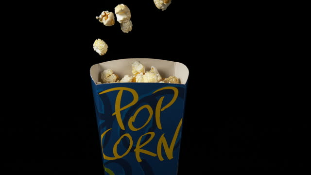 vídeos de stock, filmes e b-roll de pop corn falling into box against black background, slow motion 4k - interior