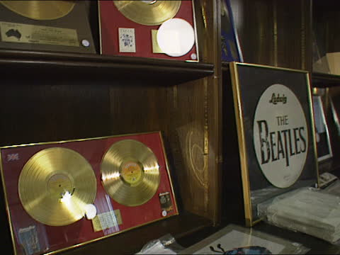 auction of beatles memorabilia cnao england london series of gold discs belonging to beatles on wall before auction tms photos of beatles in plastic... - itv lunchtime news stock videos & royalty-free footage