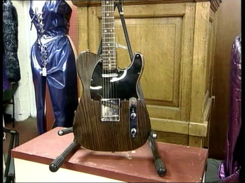 stockvideo's en b-roll-footage met george harrison guitar for sale england london bonhams former beatles member george harrison's guitar on display in auction house pull out cs guitar... - verzameling