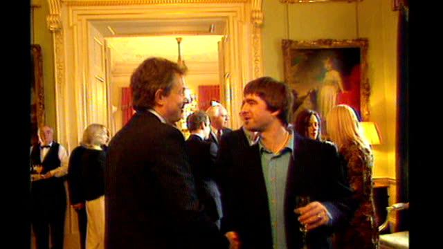 stockvideo's en b-roll-footage met oasis 20th anniversary exhibition lib / downing street number ten photography** tony blair chatting to noel gallagher at party hosted for showbiz... - tony blair