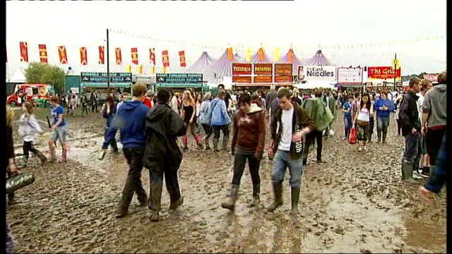 reading festival: muddy conditions; more shots of festival crowd walking along through mud - reading and leeds festivals stock videos & royalty-free footage