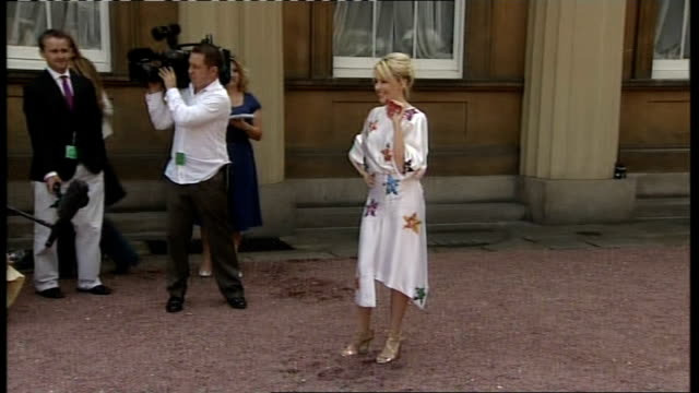 pop singer kylie minogue awarded obe: minogue mingling with guests outside palace; minogue across and posing for photocall with her obe / minogue... - autographing stock videos & royalty-free footage