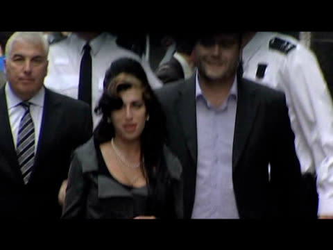 Pop star Amy Winehouse arrives at court accompanied by father Mitch and bodyguard police shield star from press 23 July 2009
