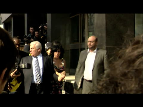 pop star amy winehouse arrives at court accompanied by father mitch and bodyguard police shield star from press london 17 march 2009 - admiration stock videos & royalty-free footage