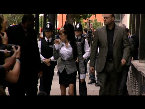 Pop star Amy Winehouse arrives at court to face assault charge and is accompanied by two bodyguards London 24 July 2009