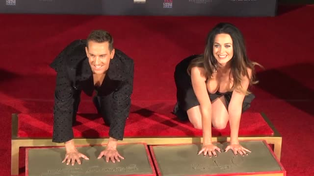us pop star katy perry has her hands imprinted in concrete outside the tcl chinese theatre on hollywood boulevard alongside fashion designer jeremy... - tcl chinese theatre stock videos & royalty-free footage
