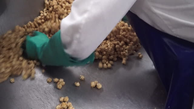 popcorn being mixed around by hand in factory - craft stock videos & royalty-free footage