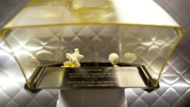 popcorn being popped in a machine, then being spit out toward the camera. - popcorn stock-videos und b-roll-filmmaterial