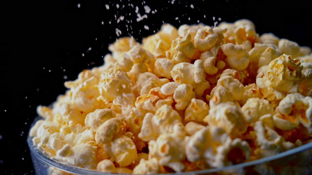 slo mo ld popcorn being sprinkled with salt - snack stock videos & royalty-free footage