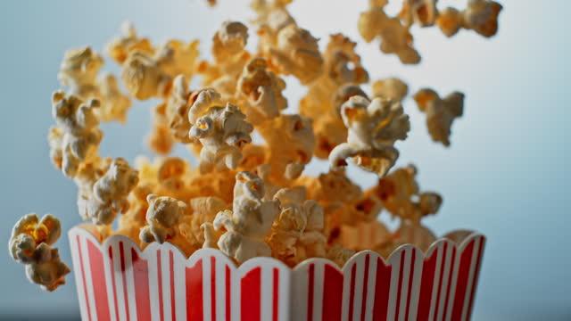 vídeos de stock, filmes e b-roll de slo mo ld pipoca saltando de uma caixa listrada - imagem a cores