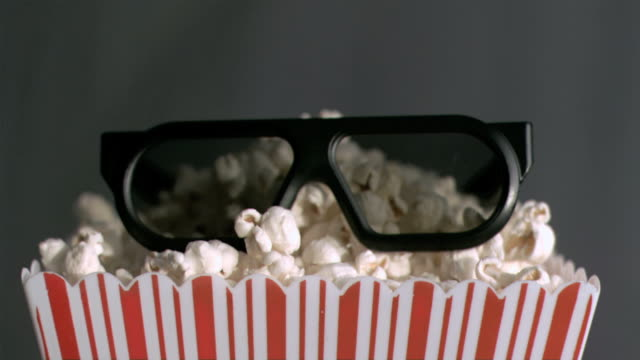vídeos de stock, filmes e b-roll de popcorn box falling in super slow motion with 3d glasses - óculos de terceira dimensão