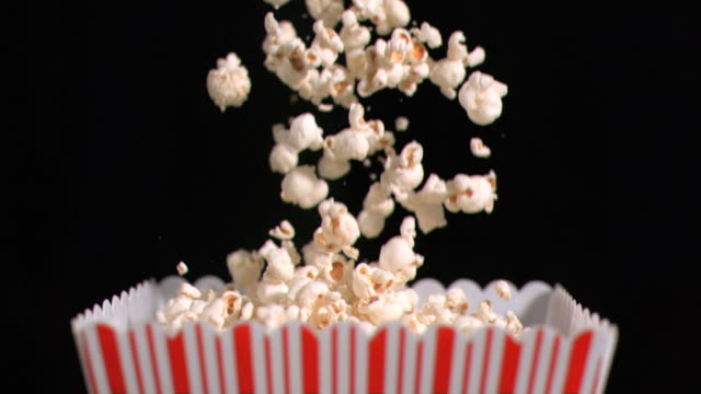 popcorn falling into bag in super slow motion - popcorn stock-videos und b-roll-filmmaterial