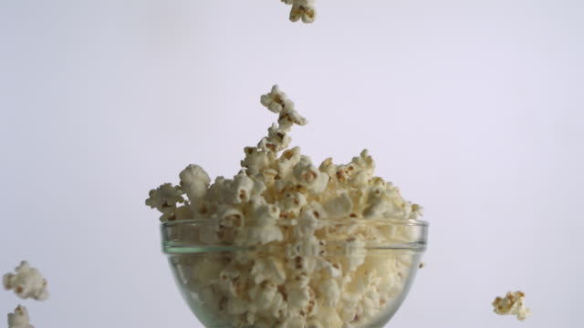 cu slo mo popcorn falling into glass against white background / new jersey, usa - popcorn stock-videos und b-roll-filmmaterial