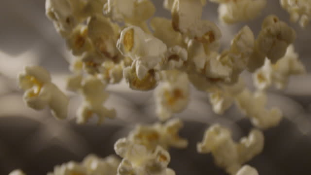 Popcorn falls across the frame, in front of a kitchen background.