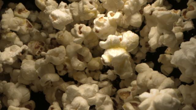 popcorn tossed up in the air against black background an overhead shot 4k - popcorn bildbanksvideor och videomaterial från bakom kulisserna