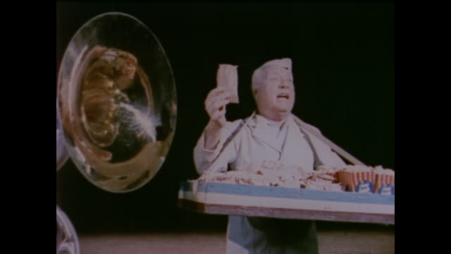 1958 popcorn vendor reacts to a blowing trumpet, demonstrating the sensation of hearing - circus stock videos & royalty-free footage