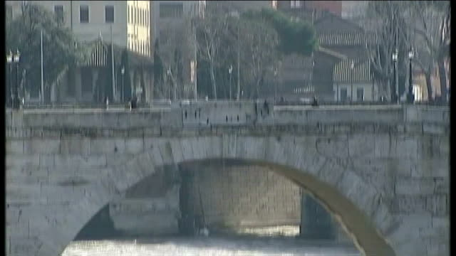 speculation mounts on his successor day church tower tilt down bridge to river tiber fast flowing water - 法王ベネディクト16世点の映像素材/bロール