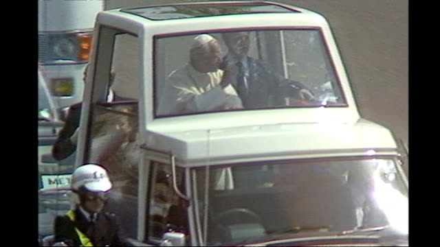 pope benedict xvi state visit: day one; 1982 london: ext various of pope john paul ii along in popemobile as arriving at buckingham palace air view... - ローマ法王専用車点の映像素材/bロール