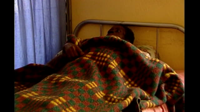 vidéos et rushes de pope claims condoms are part of reason for aids epidemic in africa; tx 1.6.2005 uganda: kampala: aids sufferers in hospital and aids poster promoting... - kampala