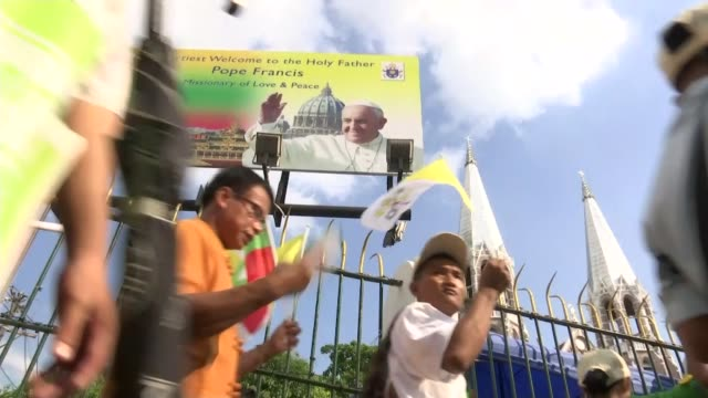 Pope Francis arrives at start of visit / Rohingya refugee crisis MYANMAR Yangon Crowds along outside church with sign advertising visit of Pope...