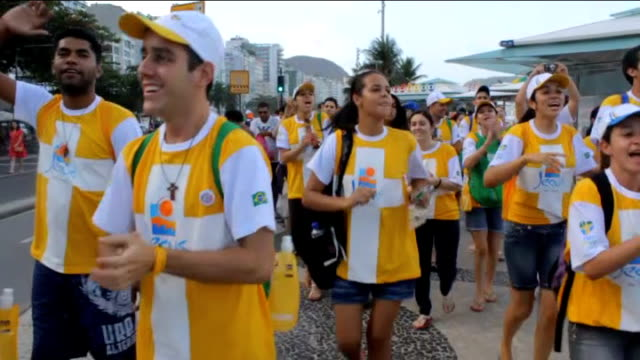 stockvideo's en b-roll-footage met pope francis arrives in brazil for visit various shots young pilgrims in yellow and white tshirts singing along road by beach christian urbine... - altaar