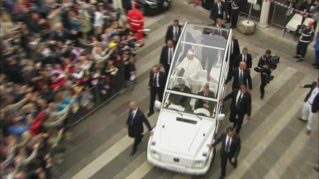 pope francis rides through a crowd in the popemobile in italy. - ローマ法王専用車点の映像素材/bロール