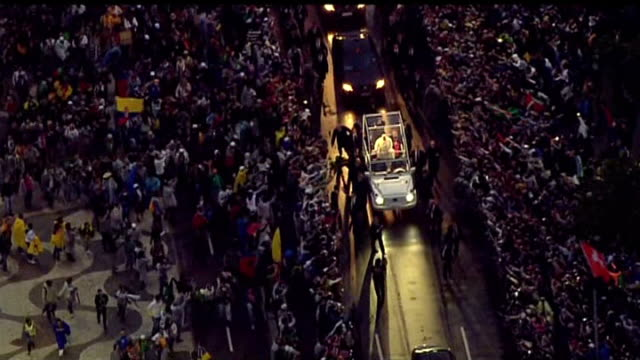pope francis visit continues; brazil: rio de janeiro: ext at night various of pope francis arriving at copacabana beach in popemobile to hold mass - ローマ法王専用車点の映像素材/bロール