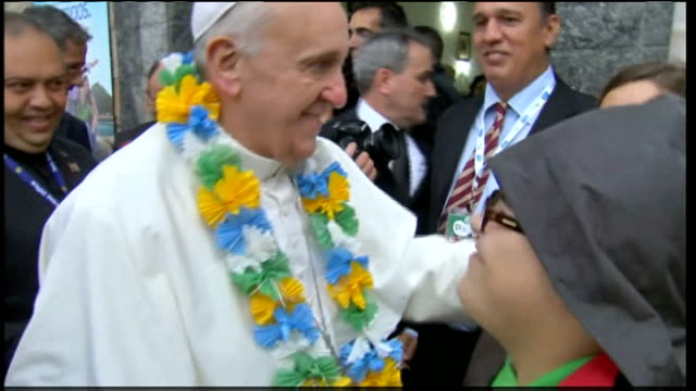 pope francis visit continues; pope france kissing woman view down on the pope as he holds up a football scarf during visit to shanty town pope... - pope stock videos & royalty-free footage