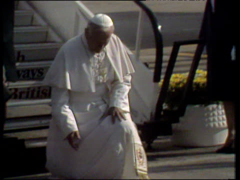 pope kneels on tarmac and kisses the ground as he leaves airplane pope john paul ii arrives in britain; 25 may 82 - pope john paul ii stock videos & royalty-free footage