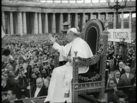 pope pius xii sits on a throne gesturing to the crowd as he moves through a crowded piazza san pietro - pope stock videos & royalty-free footage