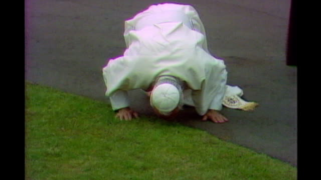 pope's visit to uk will cost taxpayers up to 12 million pounds; lib / tx 31.5.1982 scotland: edinburgh: pope john paul ii kissing ground on arrival... - pope john paul ii stock videos & royalty-free footage
