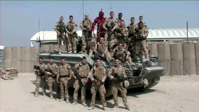 poppy appeal launched in basra; british troops sitting round table talking / desert rat badge on soldier's sleeve / soldiers talking to journalist /... - sleeve stock videos & royalty-free footage