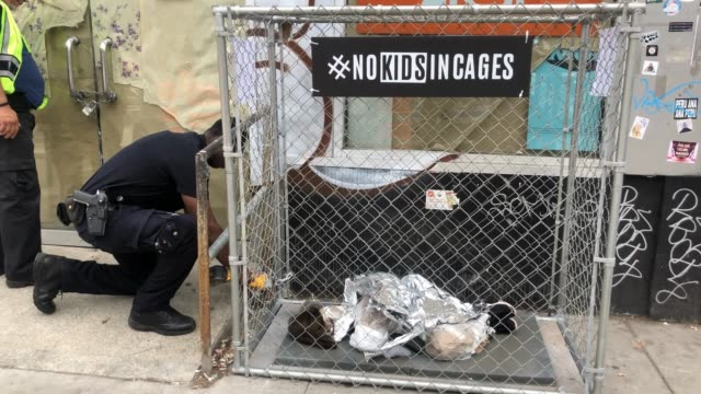 a popup art installation showing small children curled up underneath foil survival blankets in chainlink cages a depiction of migrant children in us... - curled up stock videos and b-roll footage