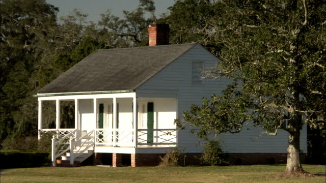 A porch fronts a small white house on the Evergreen Plantation estate. Available in HD.