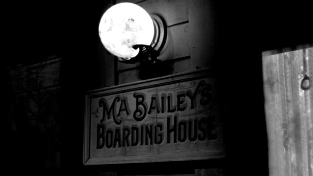 """a porch light illuminates a sign that reads """"ma bailey's boarding house"""". - western script stock videos & royalty-free footage"""
