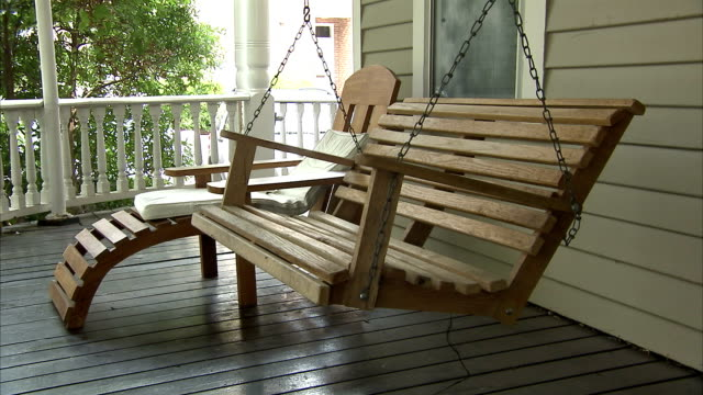 a porch swing hangs next to a lounge chair on a front porch. - chair stock videos & royalty-free footage