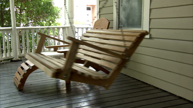 a porch swing sways next to a lounge chair. - chair stock videos & royalty-free footage