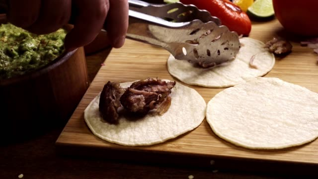 pork carnitas tacos being built on a wooden cutting board - taco stock videos & royalty-free footage