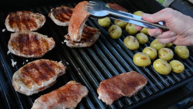 pork chops and potatoes on a grill - kotelett stock-videos und b-roll-filmmaterial