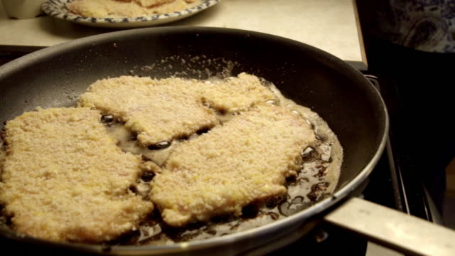 pork cutlets or schnitzel breaded and frying in a skillet - breaded stock videos and b-roll footage
