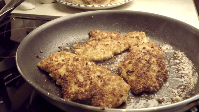pork cutlets or schnitzel breaded and frying in a skillet - frying pan stock videos & royalty-free footage