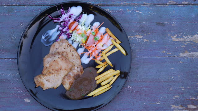 vídeos de stock e filmes b-roll de pork steak on black plate top view - ingrediente