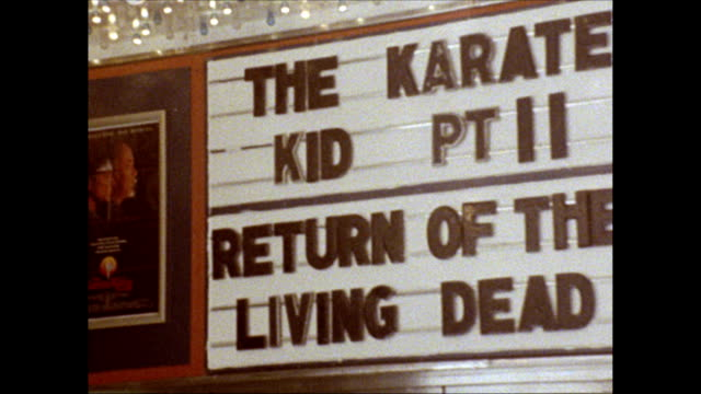 / porn theater, signs advertizing 'peep shows', hotdog stand, movie theater playing 'the karate kid part ii, and 'return of the living dead',... - theatre banner commercial sign stock videos & royalty-free footage
