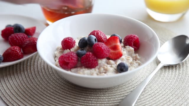 porridge being garnished with fresh berries and honey - frutta video stock e b–roll