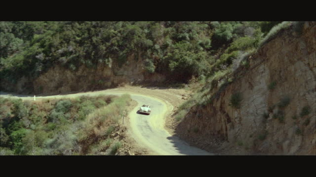 1966 aerial porsche sports car driving on mountain road - 1966 stock videos and b-roll footage