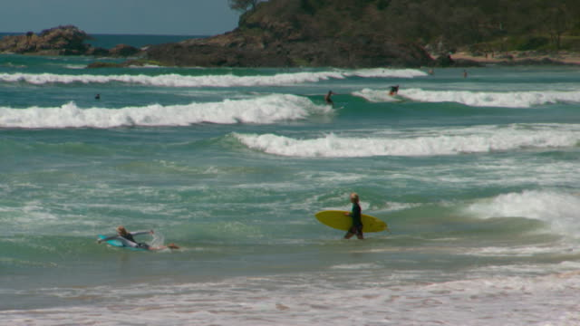 port macquarie town beach surf beach 2 anonymous boys with surfboards walk into surf one jumps on and start paddling out / wide shot and pan surf and... - diving suit stock videos and b-roll footage