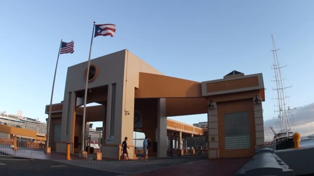 port of old san juan puerto rico on monday feb 10 wide shot of the main entrance to the port with a puerto rican and american flag blowing in the... - プエルトリコ人点の映像素材/bロール