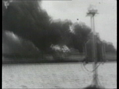 usa lib port said nov 1956 b/w british troops along on landing craft ls flames and black smoke rising from burning buildings in town tank in city... - port said stock videos & royalty-free footage
