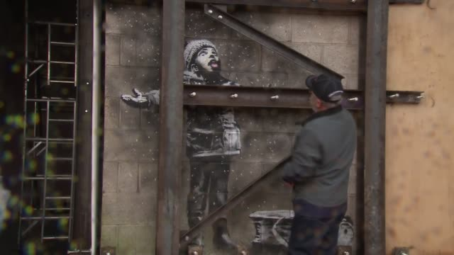 Port Talbot's Banksy artwork relocated to new home WALES Port Talbot EXT John Brandley removes protective cover as wall with Banksy mural Season's...